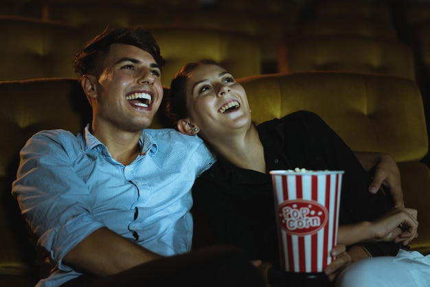 Happy young couple watching comedy movie at the cinema theater