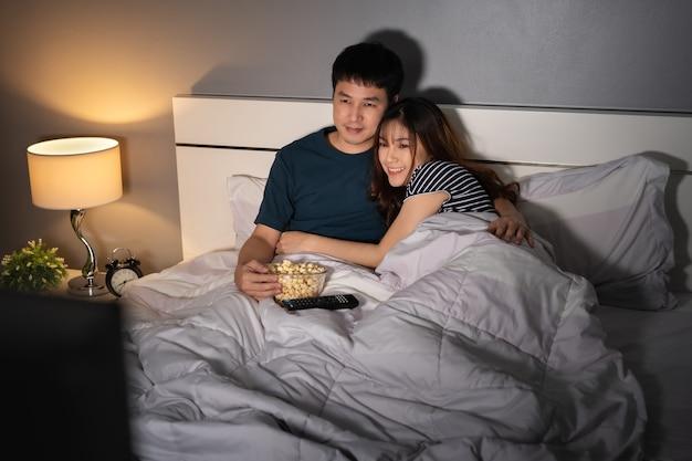 Счастливая молодая пара смотрит телевизор на кровати ночью
