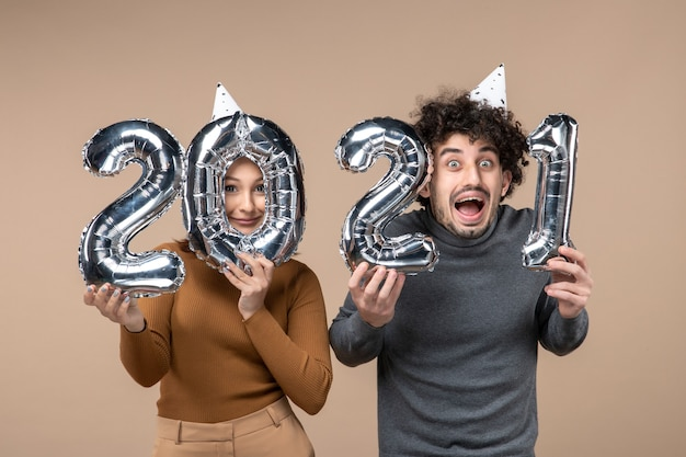 행복 한 젊은 커플 착용 새 해 모자 카메라 소녀 표시 및 남자와 회색에 대 한 포즈 스톡 사진