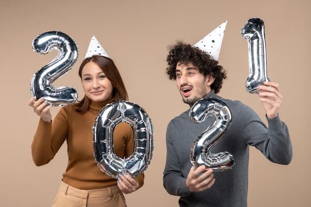 Счастливая молодая пара в новогодней шляпе позирует для камеры девушка принимает и парень смотрит в разные стороны на сером