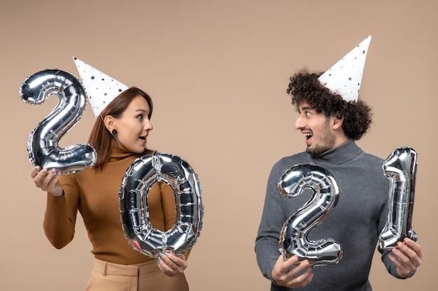 Счастливая молодая пара в новогодней шапке позирует для камеры девушка