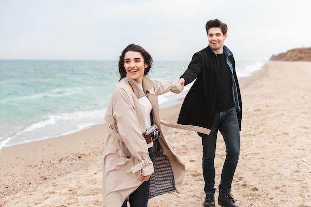 Счастливая молодая пара в осенних пальто, проводя время вместе на берегу моря, гуляя