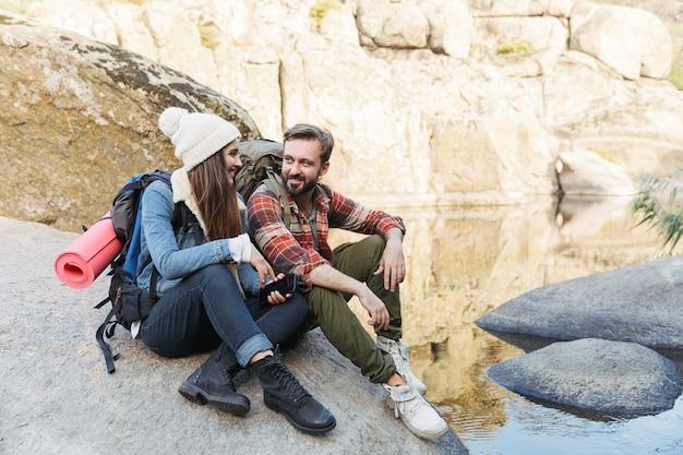 호수에 앉아 함께 하이킹 배낭을 입고 행복 한 젊은 커플