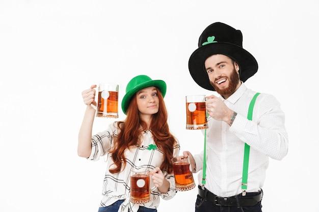 Счастливая молодая пара в костюмах, празднует день святого патрика, изолированную над белой стеной, пьет пиво