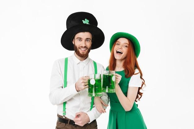 행복 한 젊은 커플 의상을 입고, 흰 벽 위에 절연 성 패트릭의 날을 축하, 맥주를 마시는