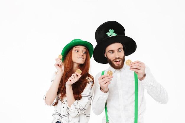 Счастливая молодая пара в костюмах, празднует день святого патрика, изолированную над белой стеной, держа золотые биткойны