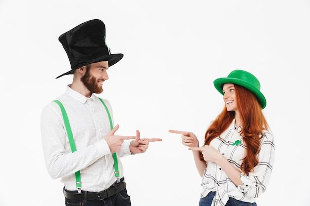 Счастливая молодая пара в костюмах, празднует день святого патрика, изолированные на белой стене, указывая пальцами