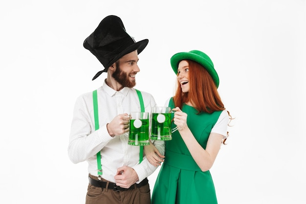 Happy young couple wearing costumes, celebrating stpatrick 's day isolated over white wall, drinking beer