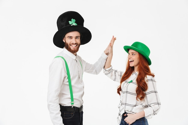 Happy young couple wearing costumes, celebrating stpatrick 's day isolated over white wall, having fun together, high five