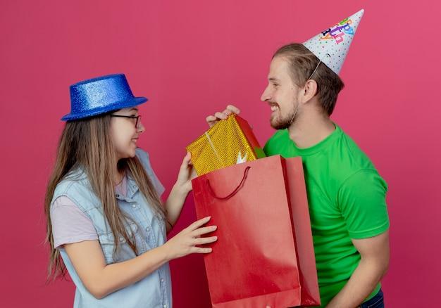 Giovani coppie felici che indossano cappelli da festa si guardano l'un l'altro e tira fuori il contenitore di regalo dal sacchetto della spesa rosso isolato sul muro rosa