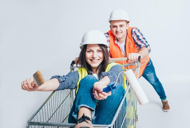 幸せな若いカップルは、新しい家の建設と修理のために買い物に行きました。