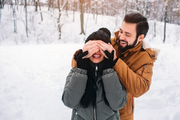 Happy young couple in winter . family outdoors. man and woman looking upwards and laughing. love, fun, season and people - walking in winter park. he covered her eyes with her hands