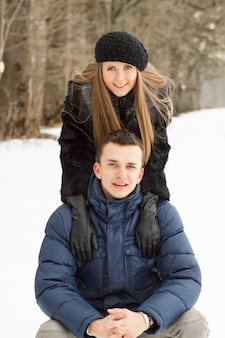 Happy young couple in winter park having fun