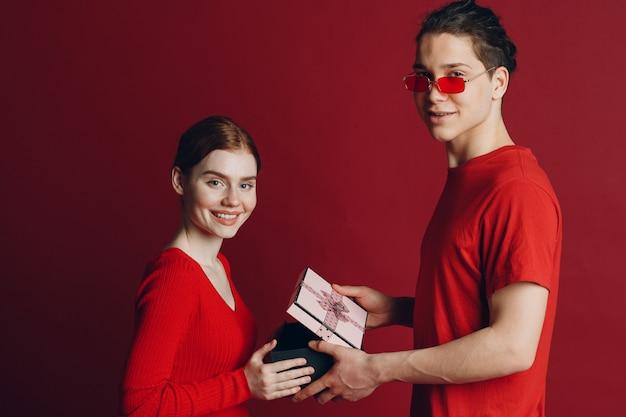 빨간색 배경에 고립 된 현재와 행복 한 젊은 커플.