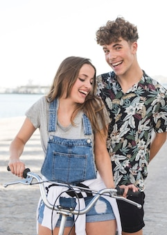 Happy young couple with bicycle at outdoors