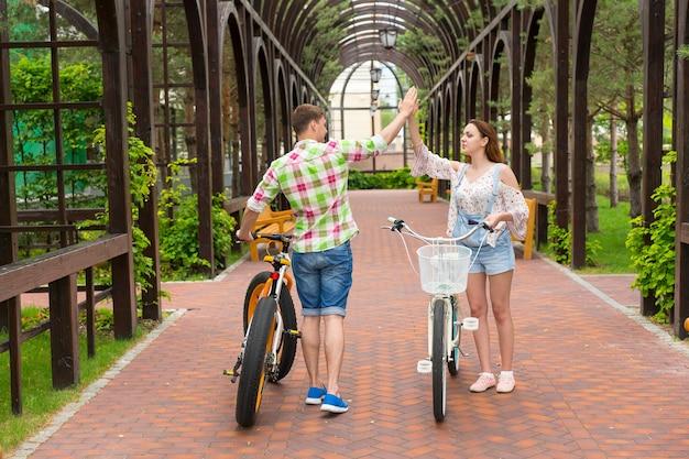 공원의 아치 밑의 통로에서 서로 하이파이브를 하는 자전거를 탄 행복한 젊은 커플