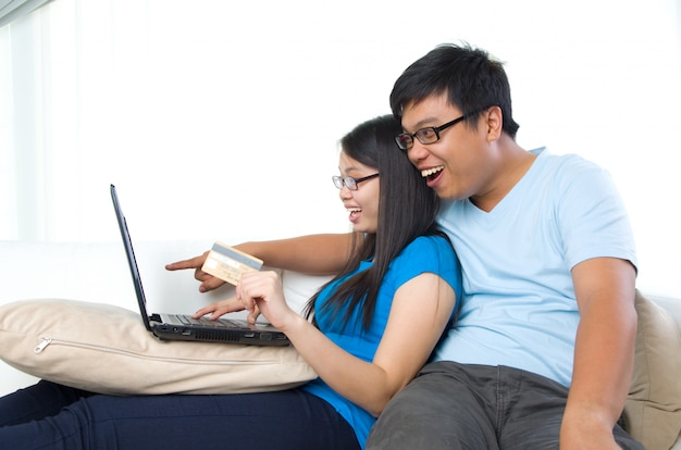 Happy young couple with credit card and laptop