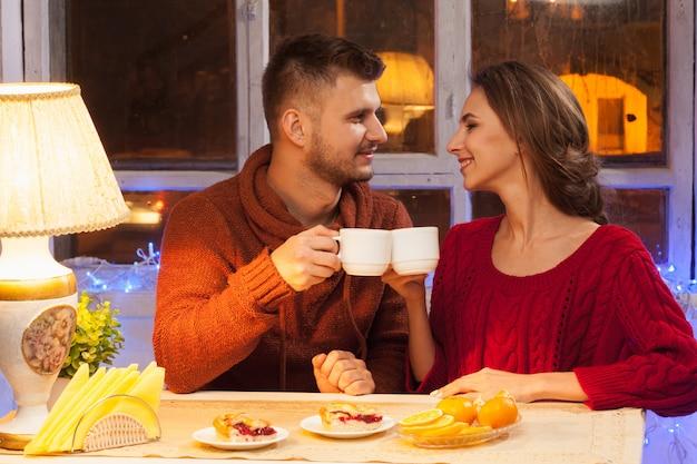 Счастливая молодая пара с чашками чая