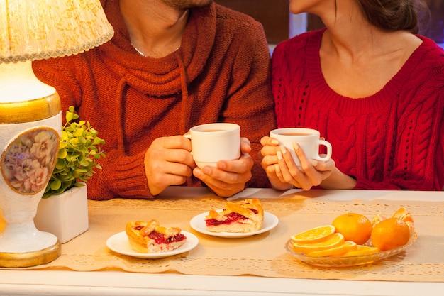 La giovane coppia felice con tazze di tè e torte.