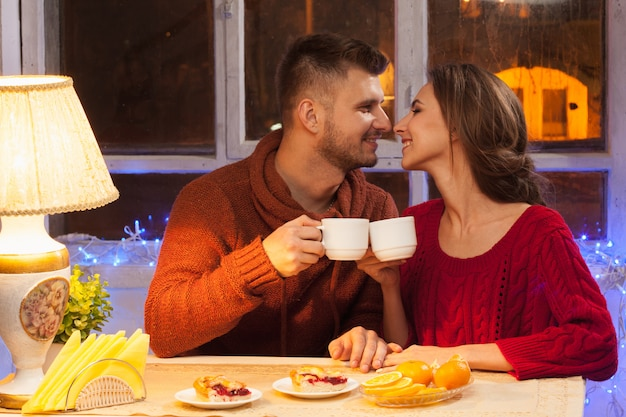 Happy young couple with cups of tea