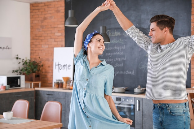 Happy young couple with dancing in kitchen at home