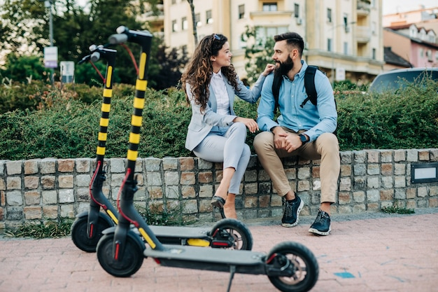 Happy young couple with electric scooters.