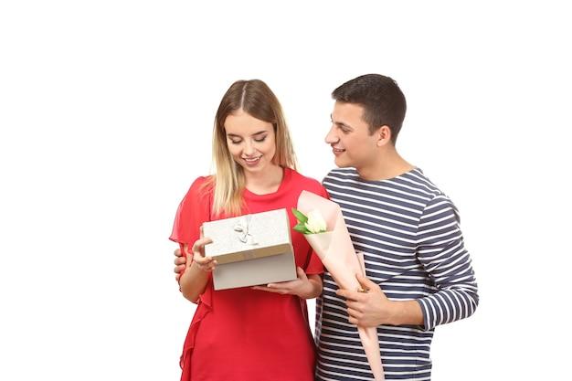 Счастливая молодая пара с подарком и цветами на белом