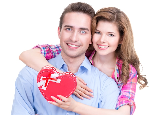 Felice giovane coppia con un regalo in uno studio isolato su uno sfondo bianco