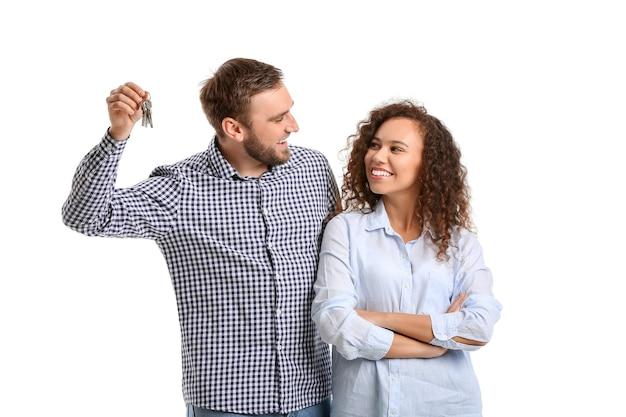 白い背景の上のキーと幸せな若いカップル