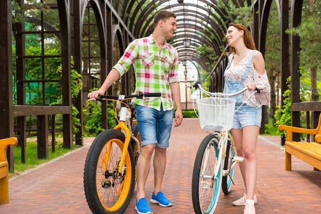 현대적인 자전거를 탄 행복한 젊은 부부는 웃고 공원의 아치형 통로에서 자유 시간을 보낸다