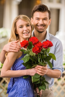Happy young couple with roses bouquet on a date.