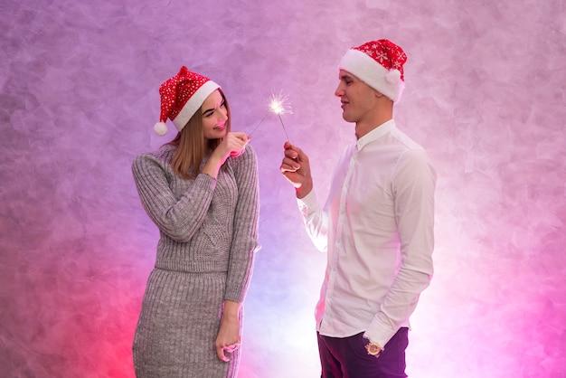 サンタの帽子とクリスマス線香花火のスタジオショットで幸せな若いカップル。