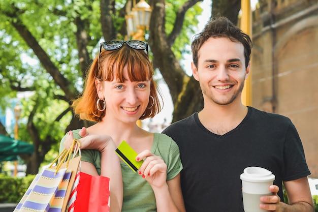 通りを歩いて買い物をした後、買い物袋を持って幸せな若いカップル。消費主義の概念。