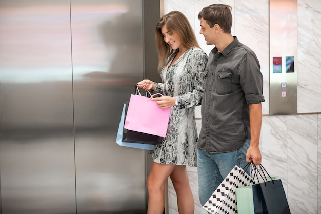 Happy young couple with shopping bags pass by the elevator, the guy enthusiastically looks at the smiling girl who opens the shopping bag. shopping. delight. sale. Premium Photo