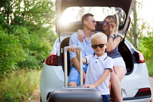 시골에서 여행하는 동안 커피를 마시고 아들과 함께 행복 한 젊은 커플. 남자와 여자가 차 트렁크에 앉아 휴식을 취하고있다.