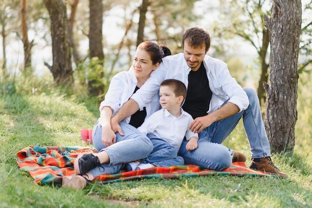 子供たちと幸せな若いカップルは自然の中で屋外の美しい公園で楽しい時を過す