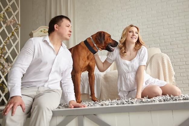 リビングルームの床に座っているペットと幸せな若いカップル