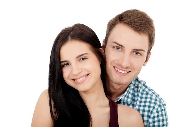 여름 의류 포용 및 흰색 배경에 카메라를 찾고 흰색 완벽한 미소로 행복 한 젊은 커플