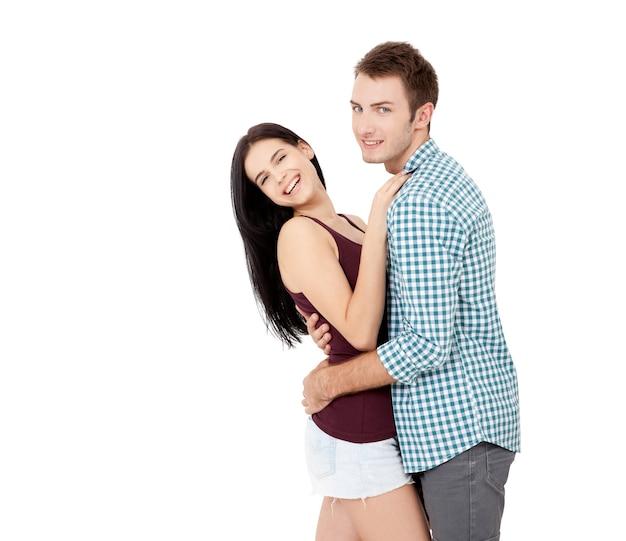흰색 바탕에 카메라를 껴안고 보고 있는 여름 옷을 입은 흰색 완벽한 미소를 가진 행복한 젊은 커플