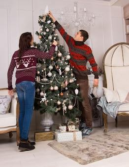 リビングルームで家族のクリスマスツリーを飾るチームとして働いている幸せな若いカップルは、最終的な装飾を一番上に置くために伸びています