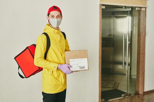 벽과 사무실 문에 카메라 앞에 서있는 손에 큰 빨간 배낭과 골판지 포장 상자와 함께 행복 한 젊은 택배