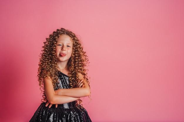 Счастливая молодая кудрявая девушка демонстрирует язык на розовом фоне
