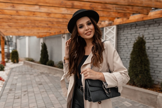 Happy young curly-haired brunette girl with a smile in fashionable clothes with a vintage hat and leather handbag walks on the street. elegant autumn female style and beauty