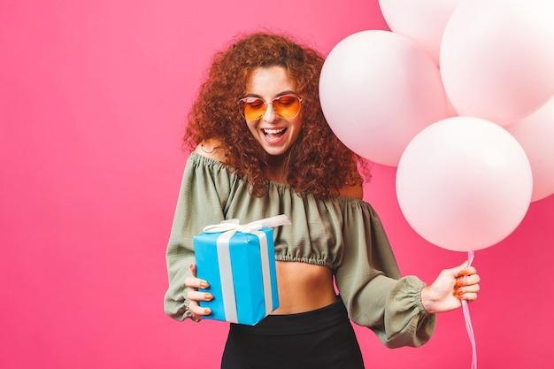 ピンクの背景に分離された風船と幸せな若い巻き毛の笑顔の女性