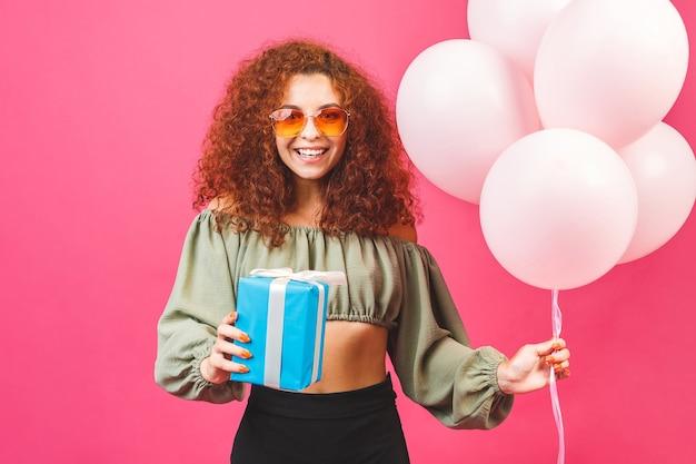 風船と幸せな若い巻き毛の笑顔の女性