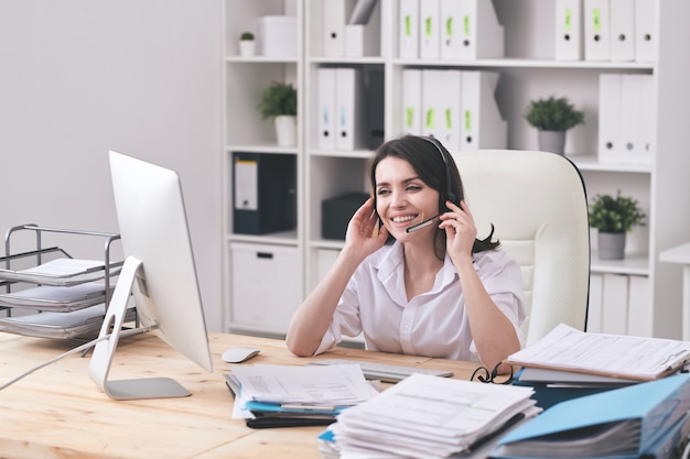 Happy young customer support representative with headset looking at client on computer screen and answering questions