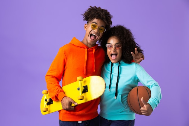 Happy young cute african couple posing isolated over violet space holding skateboard and basketball.