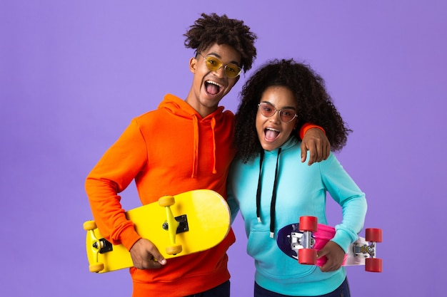 Happy young cute african couple posing isolated over violet space holding skateboards.