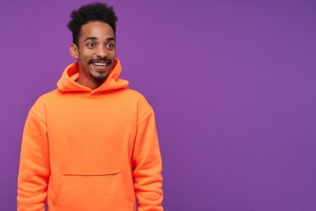 Happy young cute dark skinned brunette man with beard being pleasantly surprised and rejoicing with broad smile, dressed in casual clothes while posing on purple