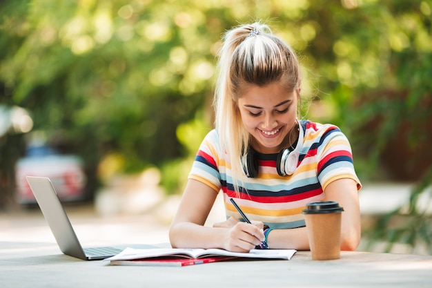 랩톱 컴퓨터를 사용하여 공원에 앉아 행복 젊은 귀여운 여자 학생.